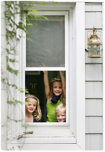 Three smiling children looking out of a window in the spring time.